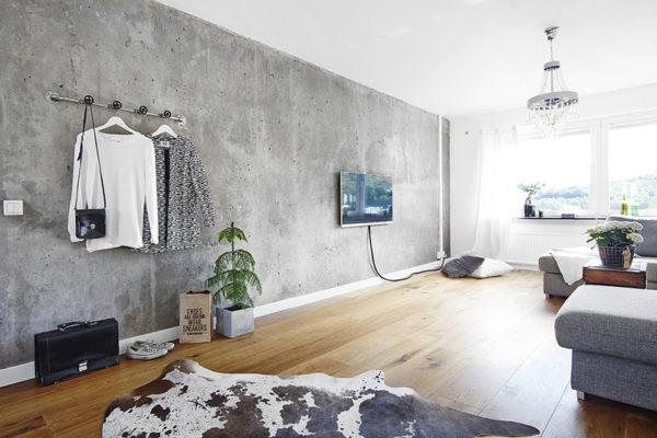 Телевизор в гостиной размещен на темной фактурной стене
