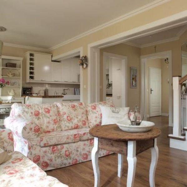Диван и кресло с цветочным пинтом в гостиной.