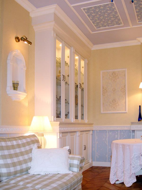 Мебель в клетку и цветные панели на потолке в гостиной